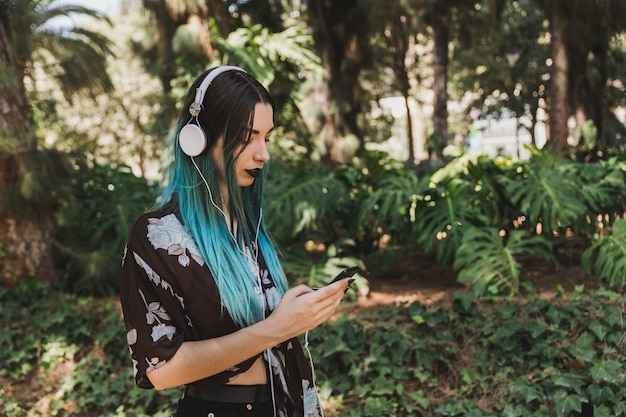 Side view of woman with dyed hair listening music on headphone using smart phone Free Photo