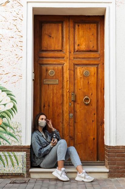 Vista laterale della donna con maschera facciale e fotocamera accanto alla porta fuori Foto Gratuite