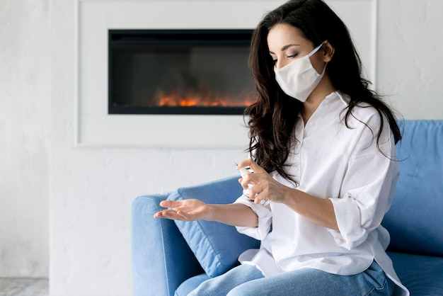 Side view of woman with face mask disinfecting her hands Free Photo