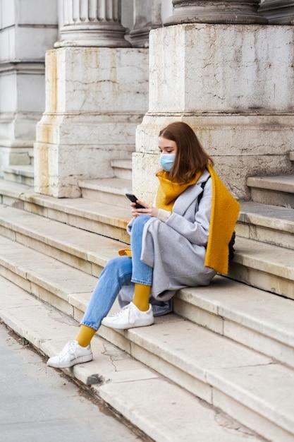 Vista laterale della donna con mascherina medica che si siede sui gradini e utilizza lo smartphone Foto Gratuite