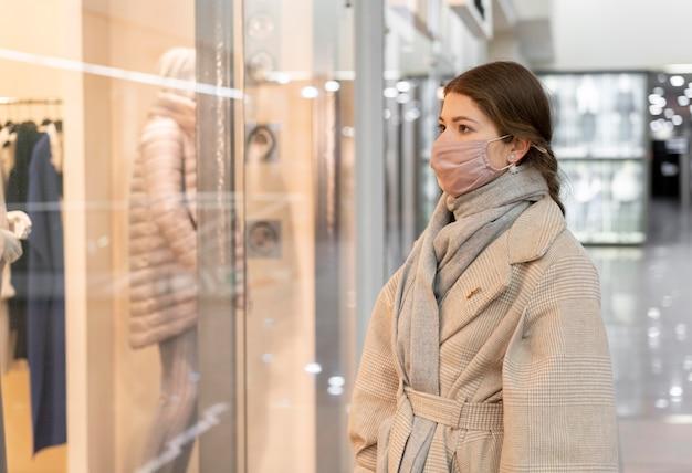 Vista laterale della donna con vetrina mascherina medica Foto Gratuite