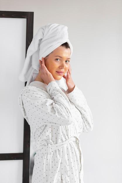 Vista laterale della donna con la cura della pelle del viso indossando accappatoio e asciugamano Foto Gratuite