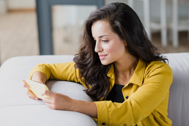 Side view woman with smartphone on sofa Free Photo