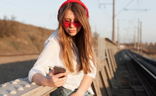 Side view of woman with sunglasses and headphones holding smartphone Free Photo