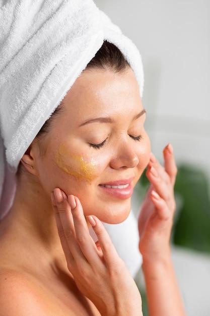 Vista laterale della donna con l'asciugamano sulla testa che applica la cura della pelle Foto Gratuite