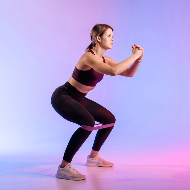 Side view woman working out with elastic band Free Photo