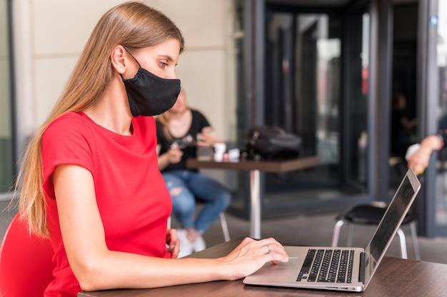 Maschera di protezione di lavoro e da portare della donna di vista laterale Foto Gratuite