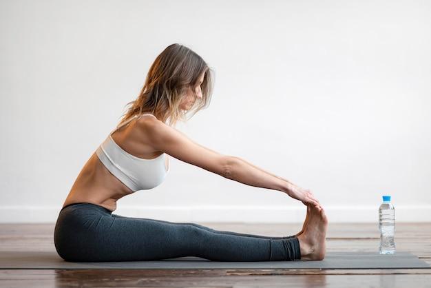 Vista laterale della donna sul materassino yoga con una bottiglia d'acqua Foto Gratuite