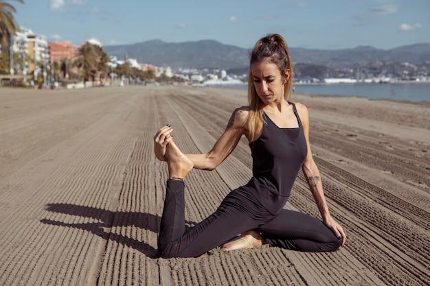 Vista laterale della donna nella posa di yoga sulla spiaggia Foto Gratuite