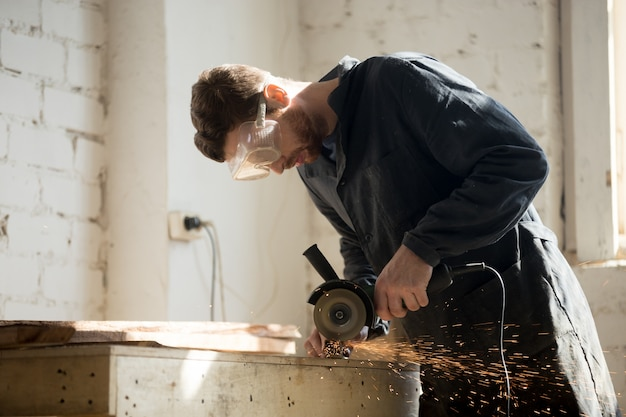 Side view of worker using angle grinder for metal cutting Free Photo