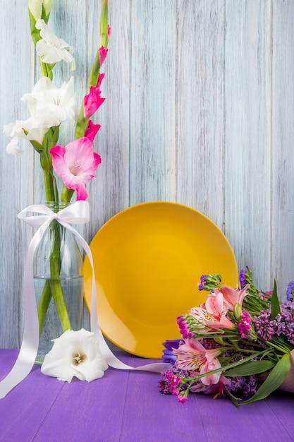 Vista laterale di un piatto di ceramica gialla con fiori di gladiolo di colore bianco e rosa in una bottiglia di vetro e con un bouquet di fiori che giace vicino su sfondo di legno grigio Foto Gratuite