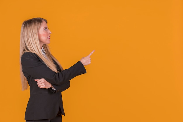 Side view of a young businesswoman pointing his finger against backdrop Free Photo