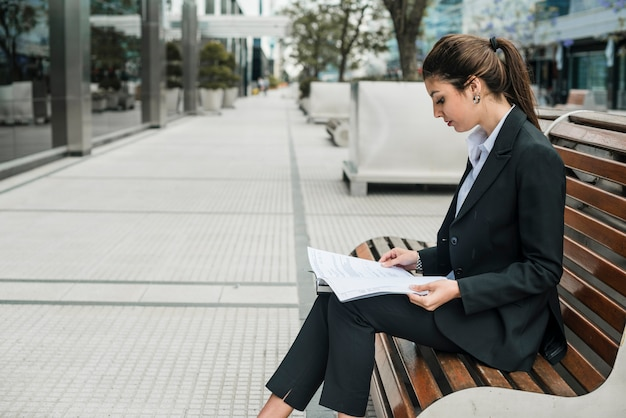 Side view of a young businesswoman sitting on bench reading the documents paper Free Photo