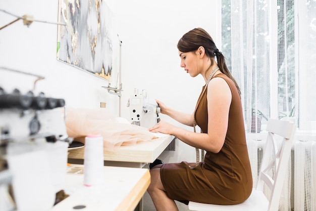 Side view of a young female designer working on sewing machine Free Photo