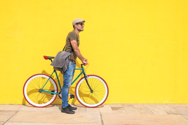 Side view of a young hipster man with a fixed bike Premium Photo