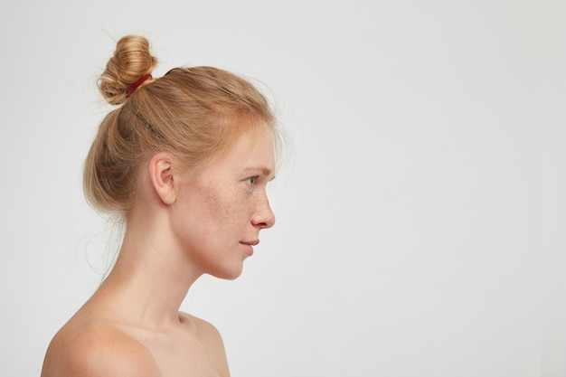 Side view of young lovely redhead female with casual hairstyle looking in front of herself with calm face and keeping her lips folded, isolated over white background Free Photo