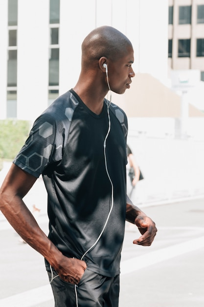 Side view of a young male athlete with hand in his pocket listening music on earphones Free Photo