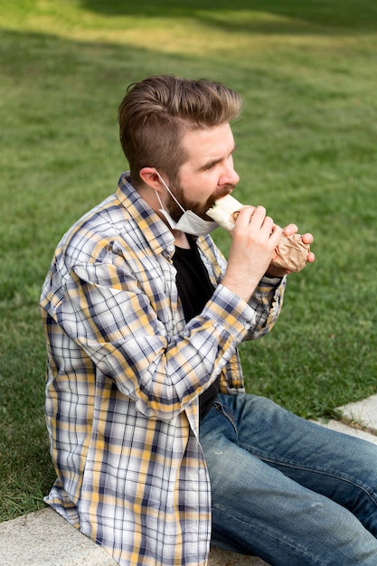 Вид сбоку молодой мужчина ест фаст-фуд Бесплатные Фотографии