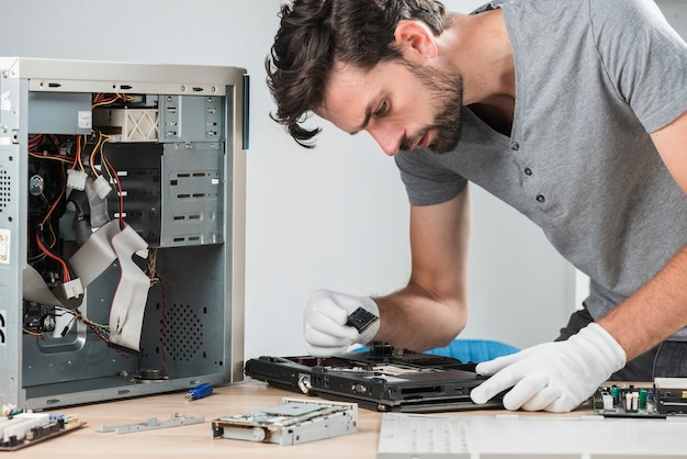 Side view of a young male technician examining laptop ram Premium Photo