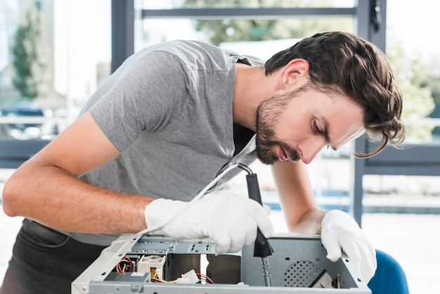 Side view of a young male technician working on broken computer Free Photo