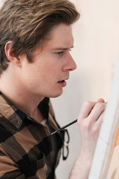 Side view young man artist painting Free Photo