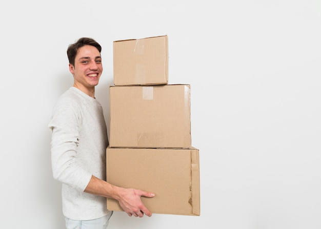 Side view of a young man carrying the stack of cardboard boxes against white wall Free Photo