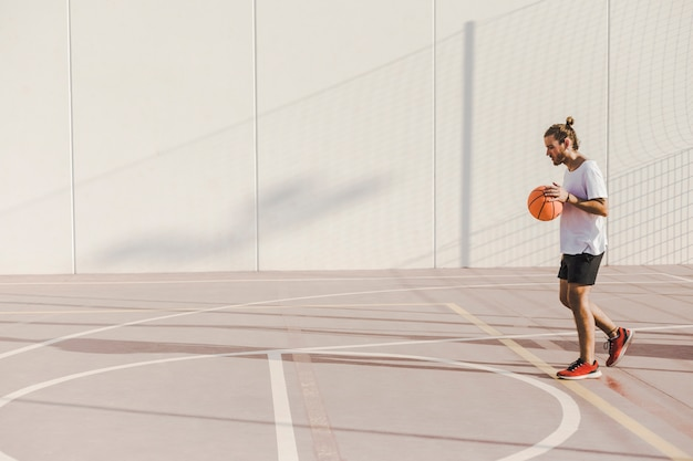 Side view of a young man playing basketball in court Free Photo