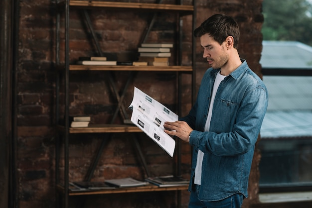 Side view of a young man reading magazine at home Free Photo