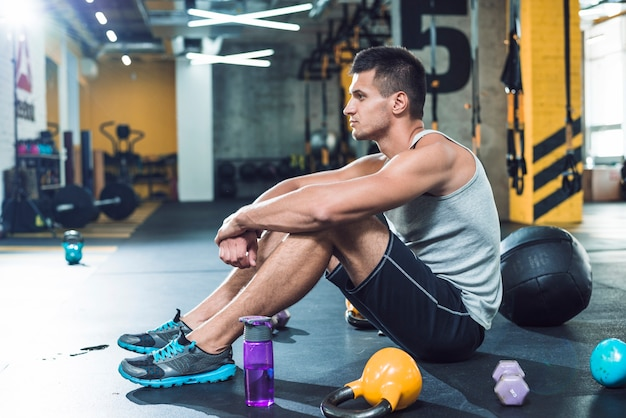 Side view of a young man sitting on floor near exercise equipments and water bottle Free Photo