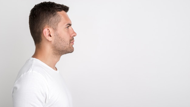 Side view of young man standing against white background Free Photo