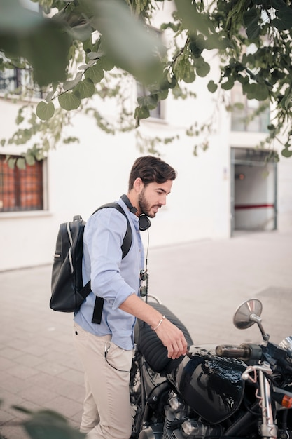 Side view of a young man standing with his motorbike Free Photo
