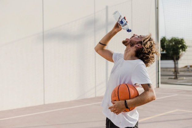Side view of a young man with basketball drinking water Free Photo
