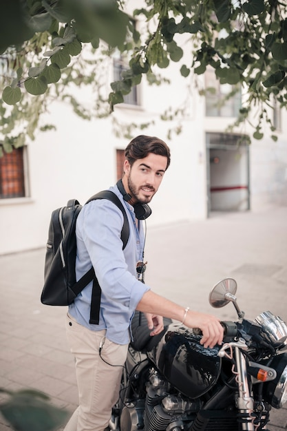 Side view of a young man with his motorbike Free Photo