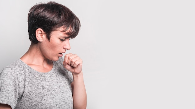 Side view of young woman coughing against gray background