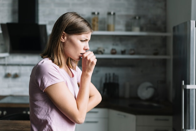 Side view of a young woman coughing at home Premium Photo