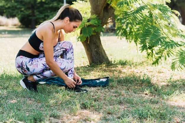 Side view of a young woman in the garden tying her shoelace Free Photo
