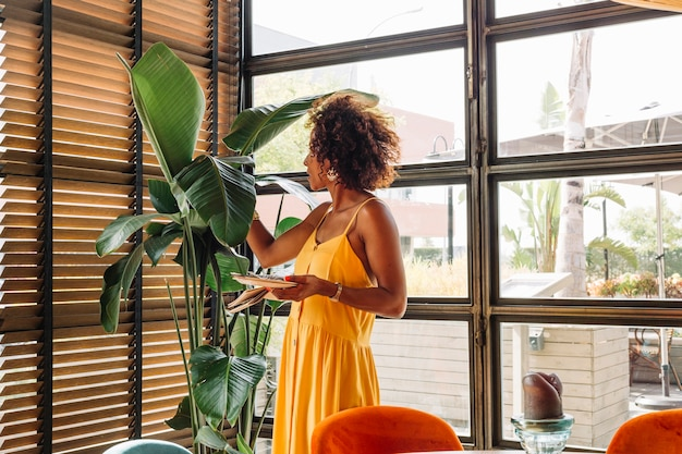 Side view of young woman holding plate standing near the plant Free Photo