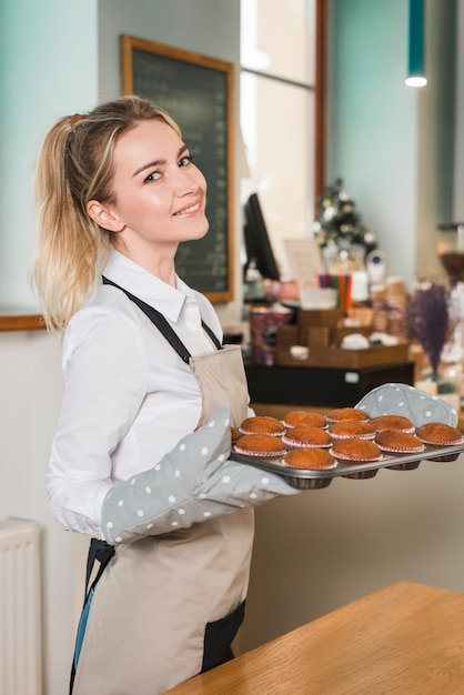 Side view of a young woman holding tray of fresh baked muffins Free Photo