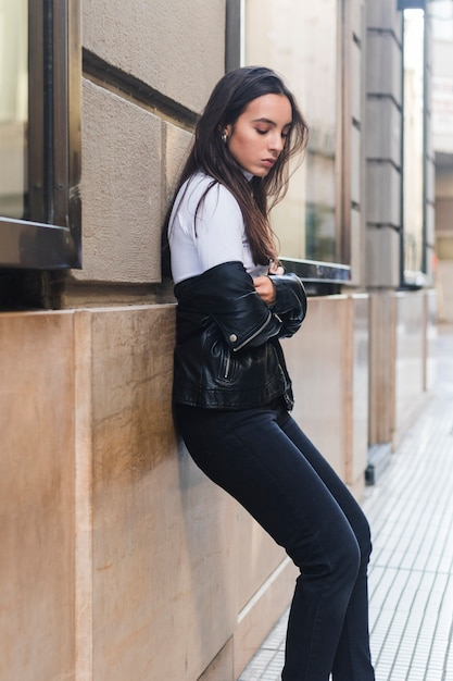 Side view of a young woman leaning on wall by the sidewalk Free Photo