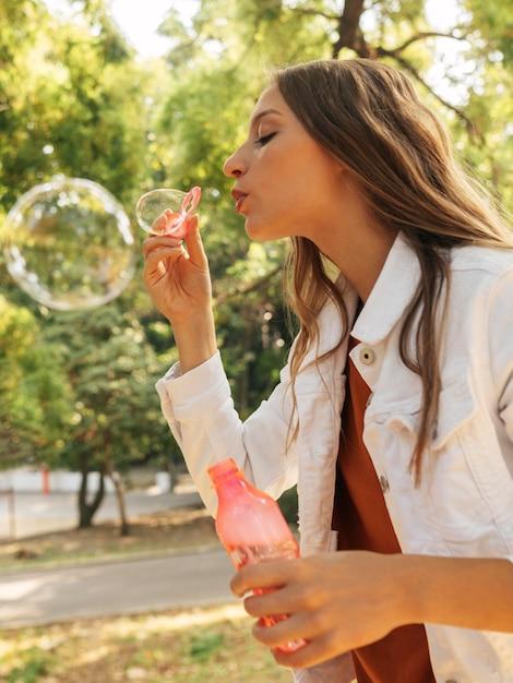 Giovane donna di vista laterale che fa le bolle di sapone Foto Gratuite