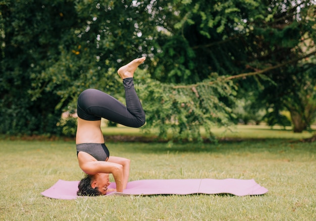 Side view of a young woman practicing yoga in the park Free Photo
