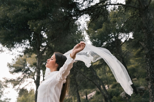 Side view of a young woman raising her hands flying scarf and enjoying the fresh air in the forest Free Photo