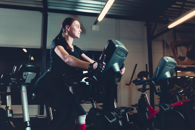 Side view of a young woman riding on exercise bike in gym Free Photo