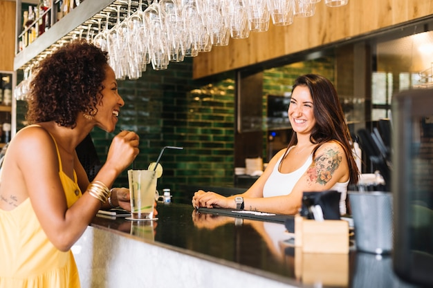 Side view of young woman smiling with female bartender at bar counter Free Photo