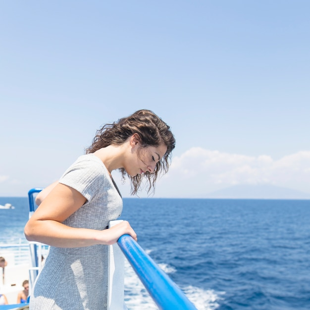 Side view of young woman standing near railings looking at blue sea Free Photo