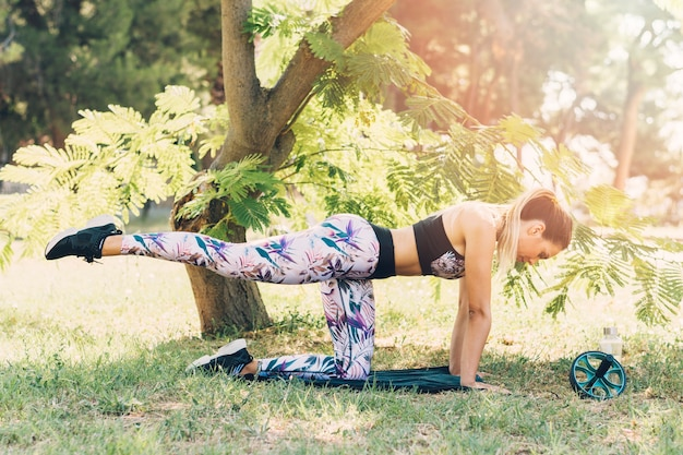 Side view of a young woman stretching under the tree in the park Free Photo
