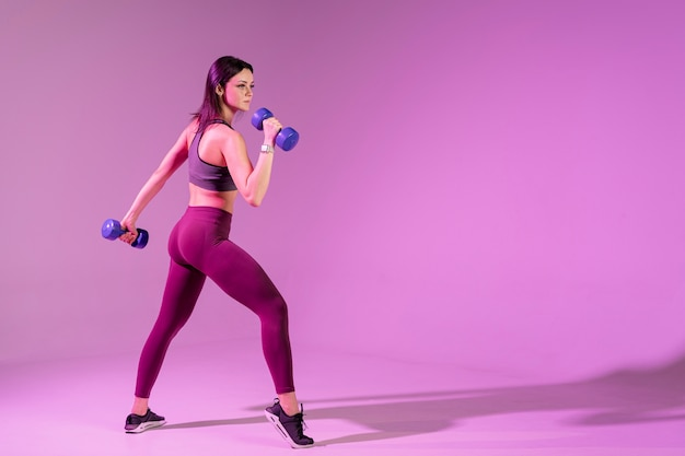 Side view young woman training with weights Free Photo