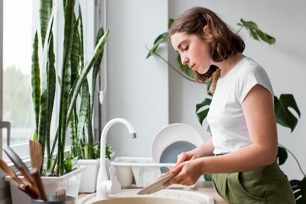 Вид сбоку молодая женщина, мытье посуды Бесплатные Фотографии