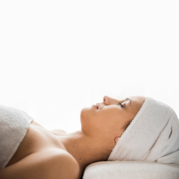 Side view of young woman with wrapped towel on her head sleeping over massage bed against white backdrop Free Photo