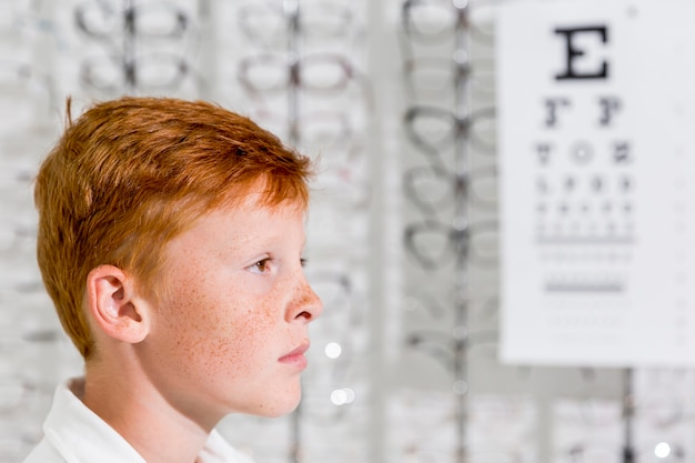 Side of young adorable boy with freckle on his face standing in optics shop Free Photo